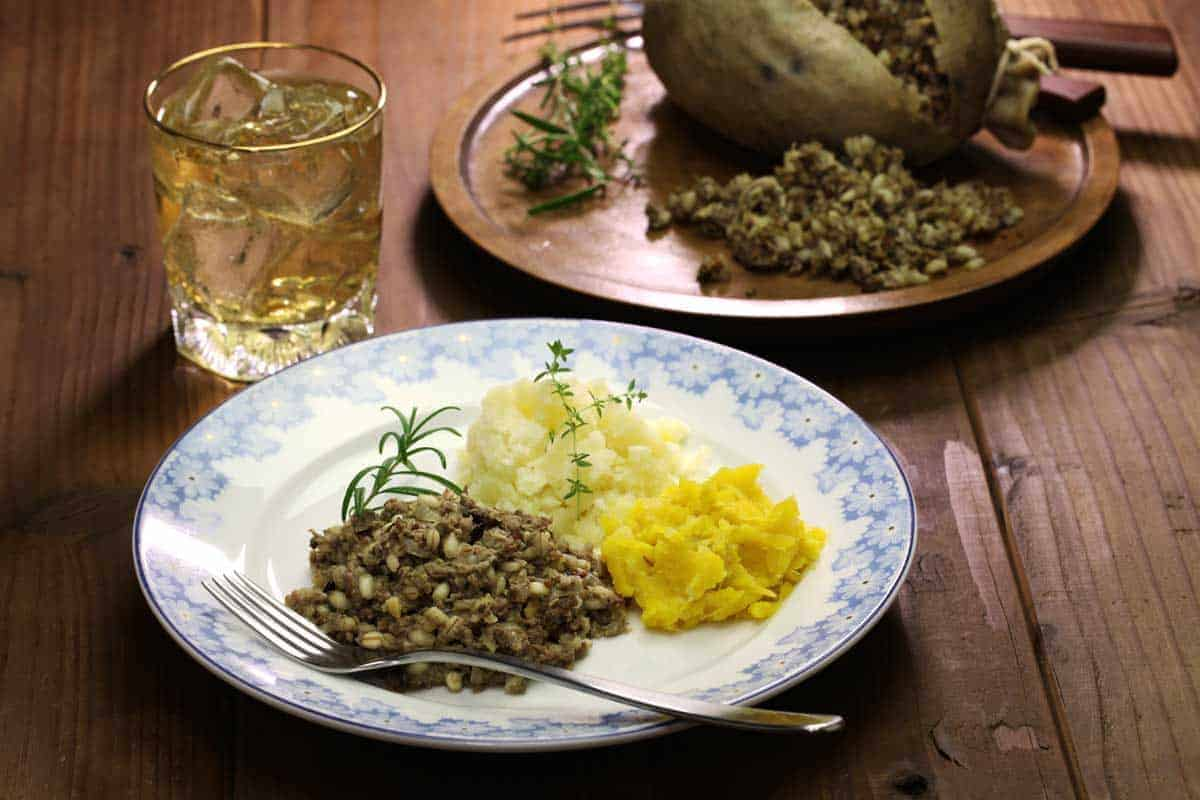 Plate of traditional haggis neaps and tatties with a glass of whiskey.