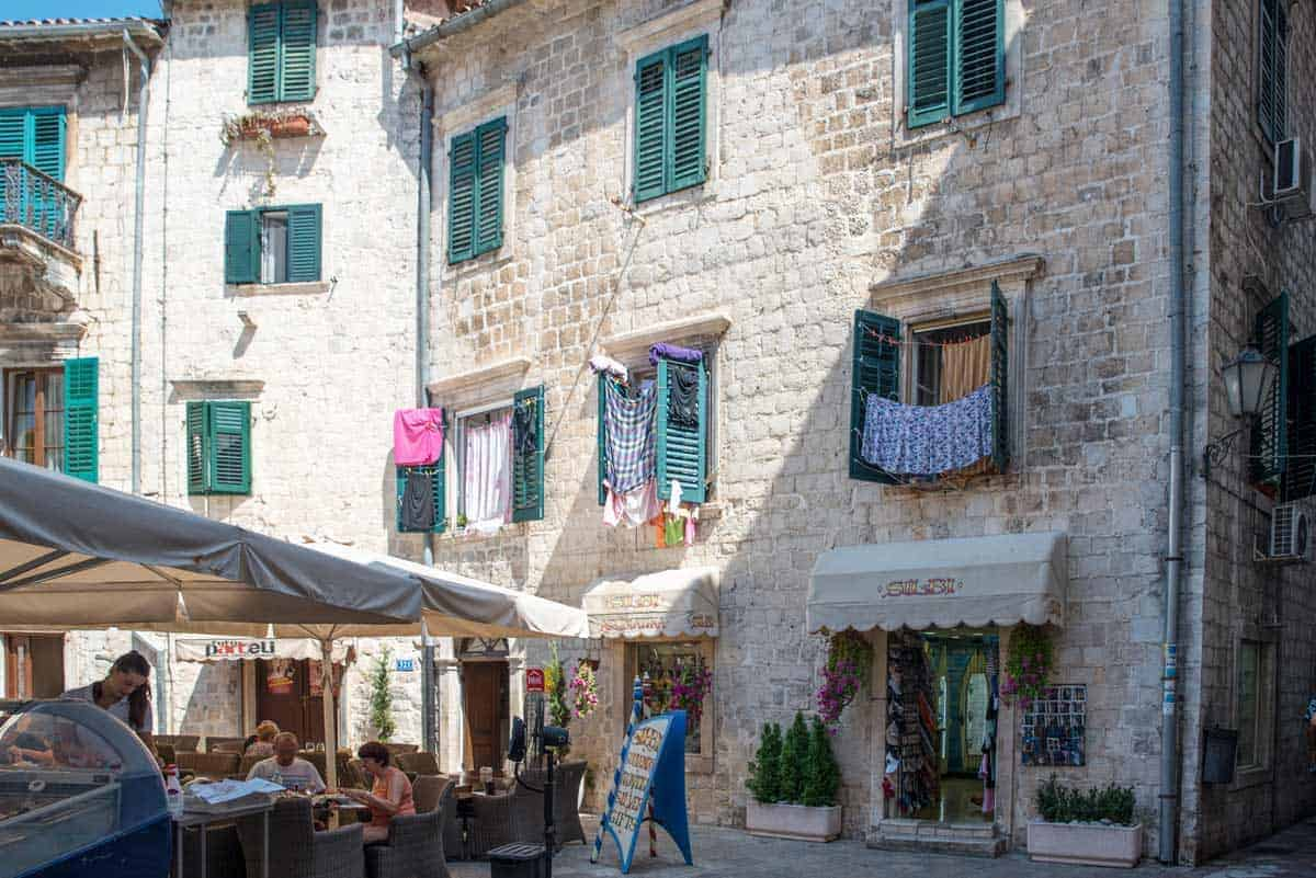 Old Town Kotor with typical restaurants and washing hanging from windows.