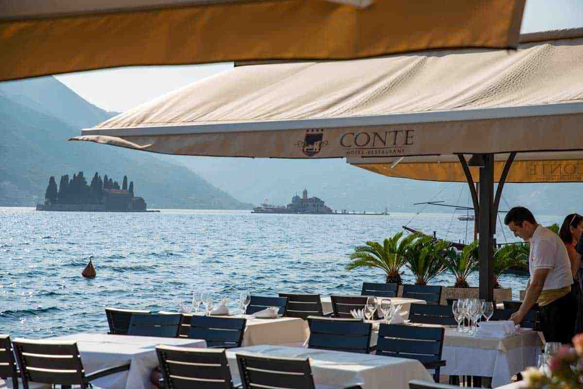 Waterside restaurant in Perast with Our Lady of the Rocks island in the background.