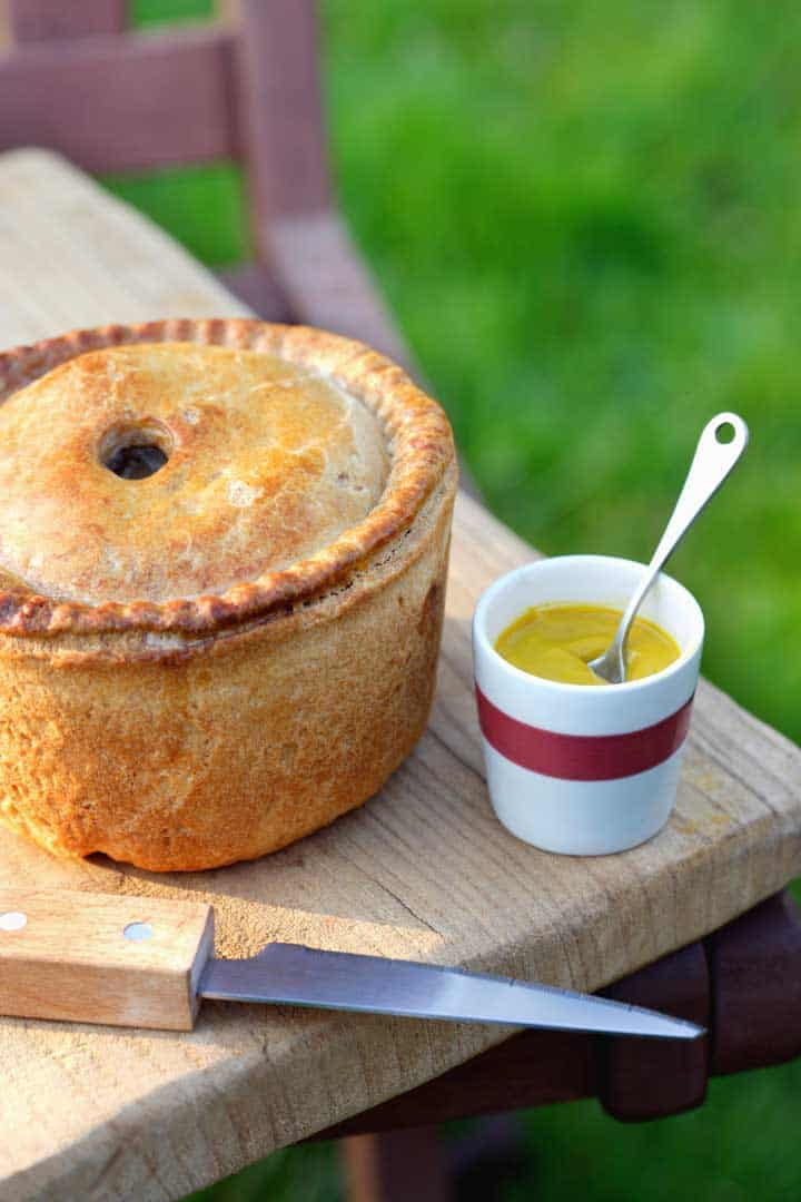 Pork pie with a small bowl of mustard.