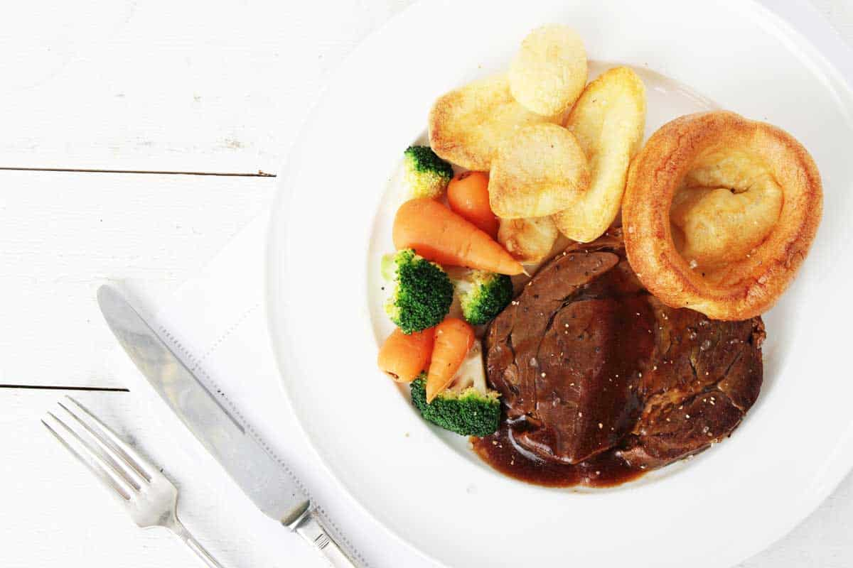 Typical roast beef dinner with vegetables and Yorkshire puddings.