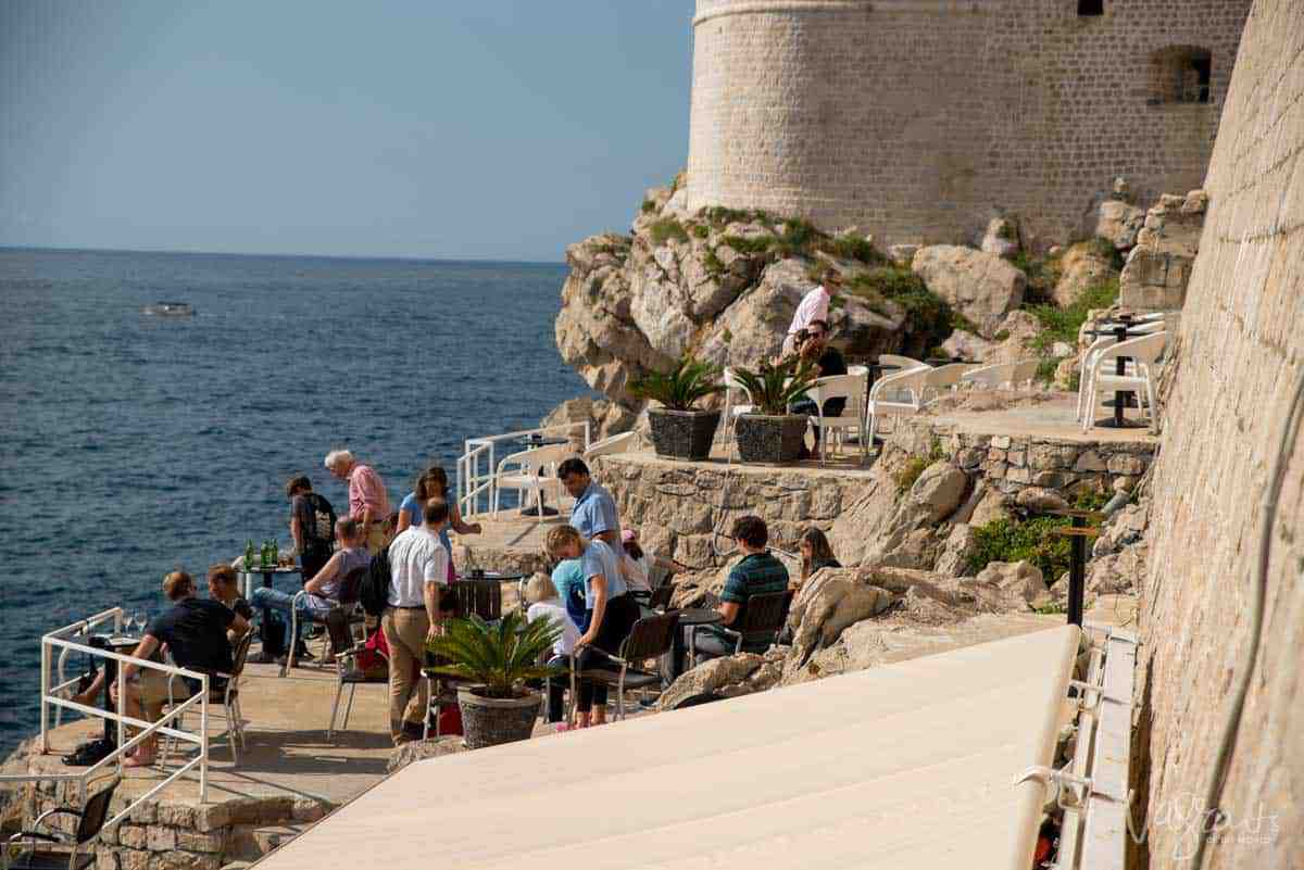People waiting for sunset over the Adriatic on the cliffside bar outside the walls of Dubrovnik Old Town.