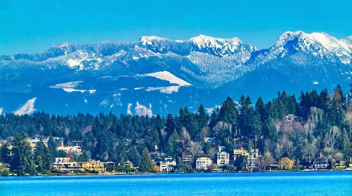Bellevue Washington with the lake in the forground and snow capped mountains behind.