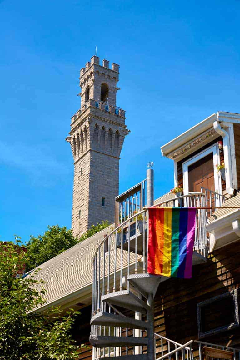 The Pilgrim monument tower in Provincetown Cape Cod with a LGBTQ flag on a balcony in the foreground.