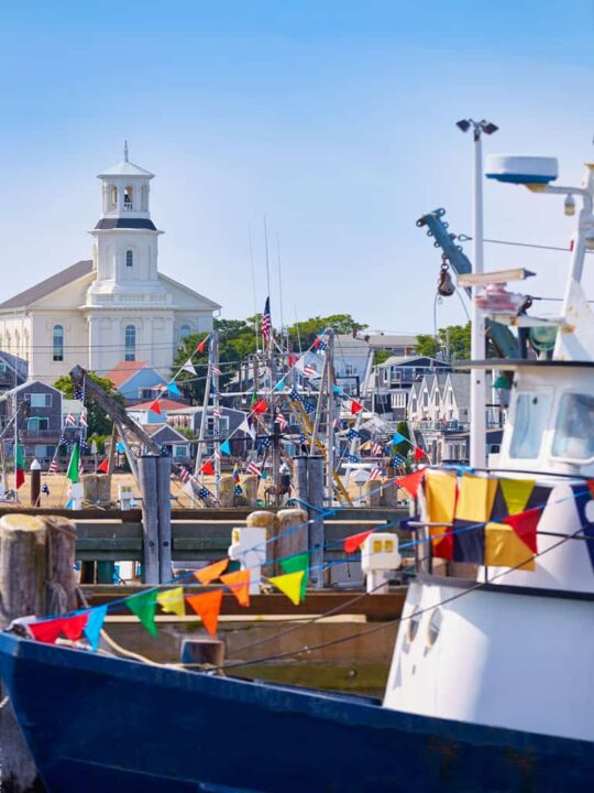 Fishing boats with bright flags in the harbor of Princetown Cape Cod.