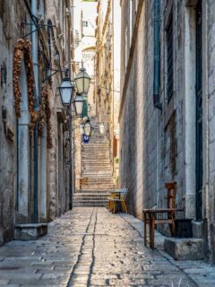A narrow, empty side street in Dubrovnik Old Town with the iconic steep stairs at the end.