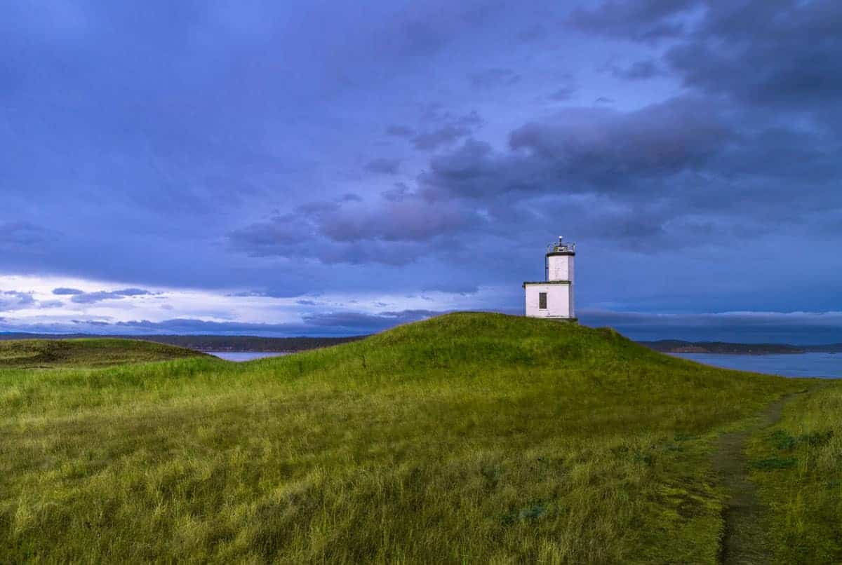 Lighthouse against a blue dusk sky and bright grass meadow in the foreground.