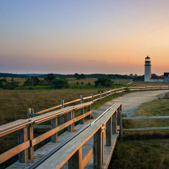 Race Point lighthouse at sunset with fields and boardwalk in the foreground.