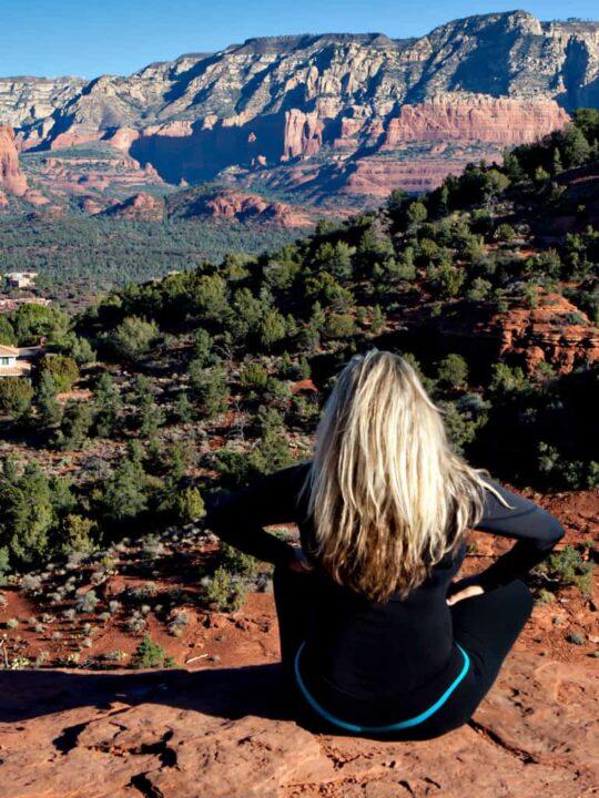 Blonde woman sitting crossed legged on rocks over looking a valley inn Sedona.