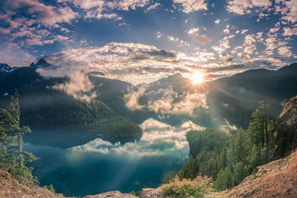 Shining sunset and fog patches over lake and mountains at North Cascade National Park
