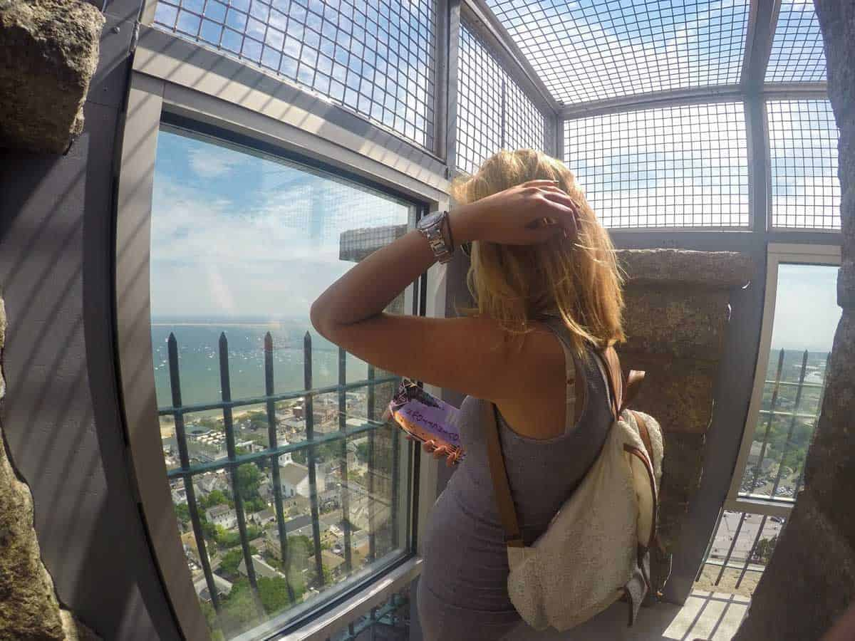 Young woman admiring the views from the top of the Pilgrim Monument in Cape Cod.