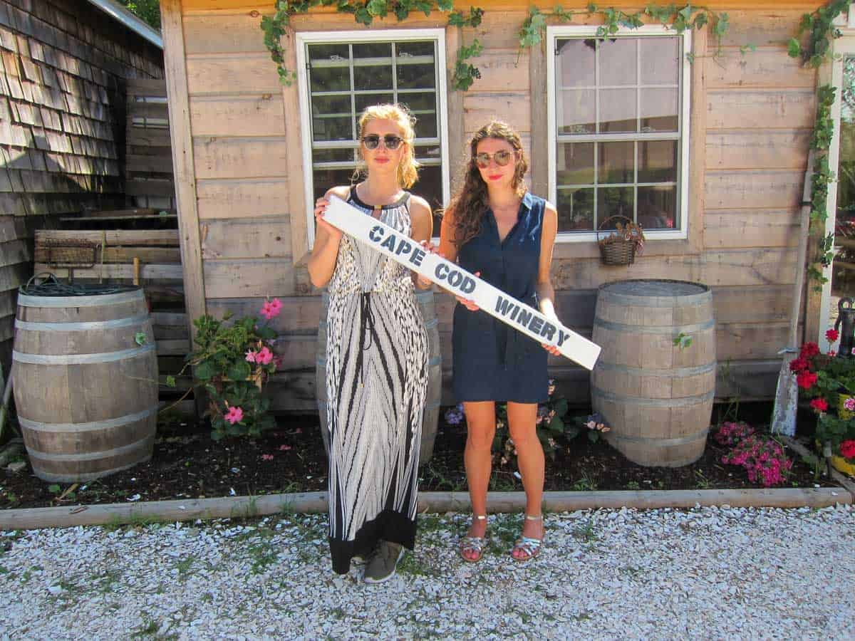 """Two attractive young women holding a """"Cape Cod Winery sign outside a vineyard."""