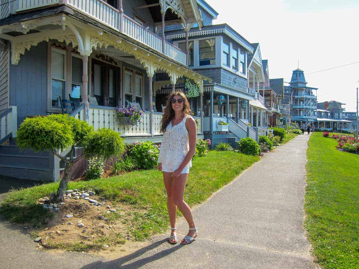 Young girl posing on the sidewalk in front of the Gingerbread houses of Martha's Vineyard.