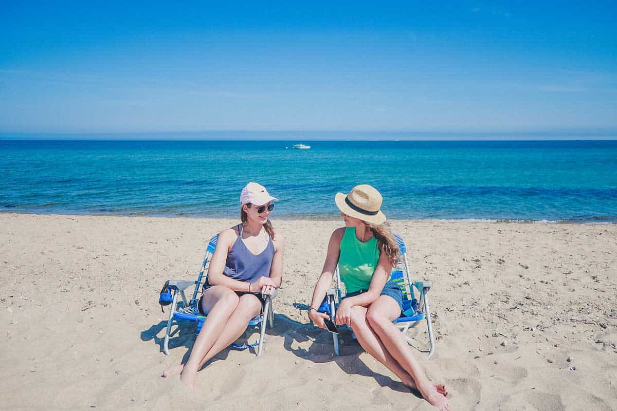 Two young women sitting on beach chairs on the beach in Cape Cod in front of the sea.