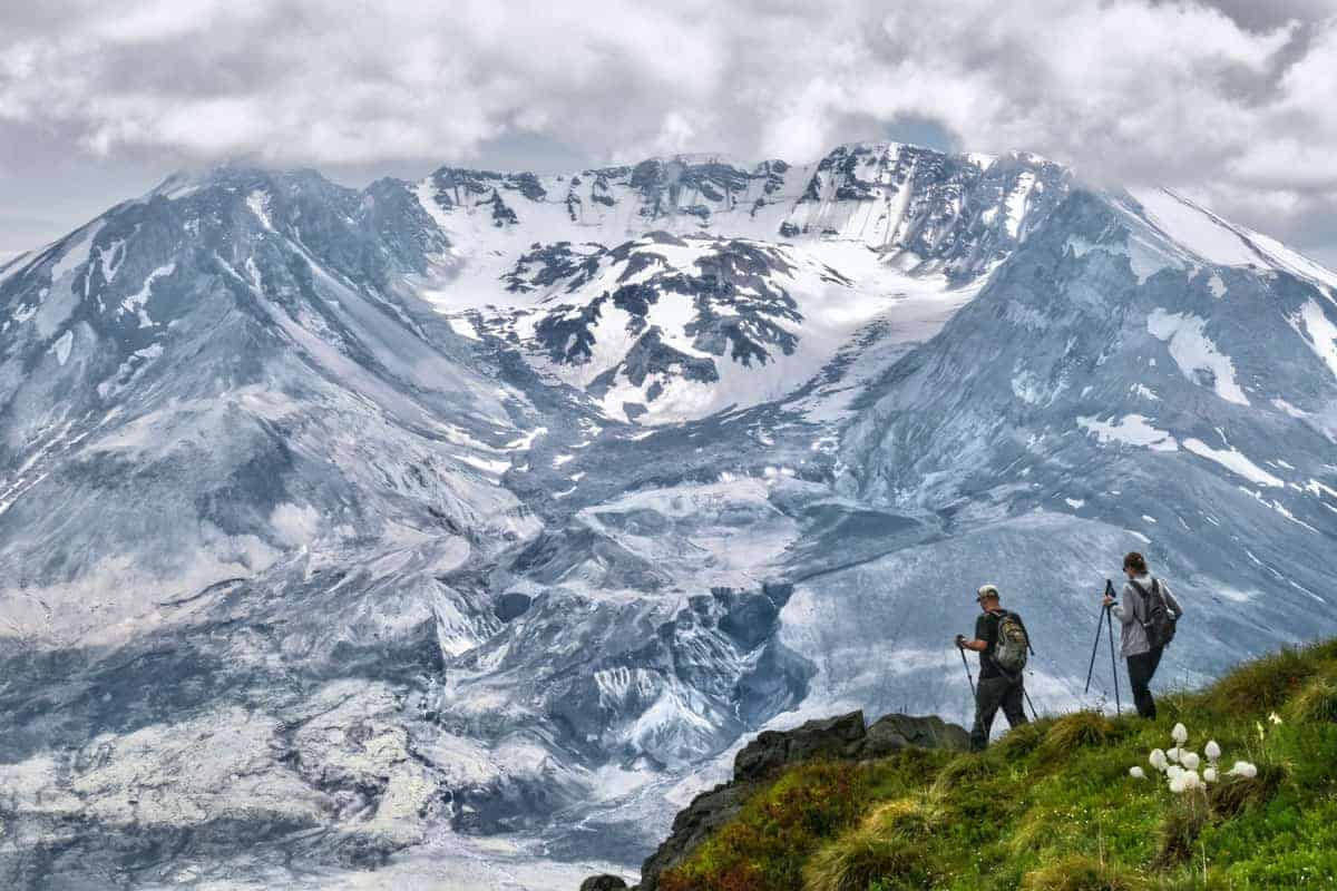 COuple trekking around Mount ST. Helen on a grassy outcrop against the white volcanic mountain.