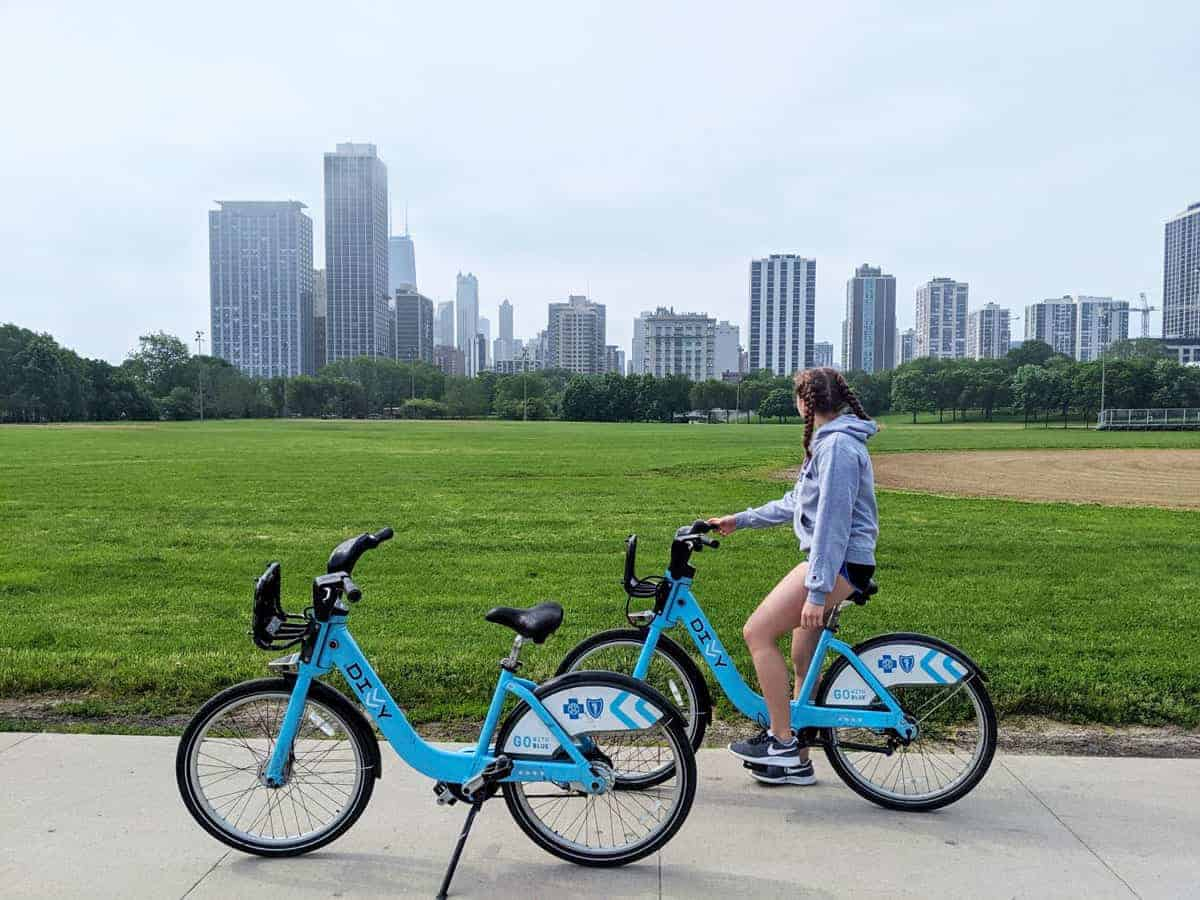 Young girl on a rental bike with Chicago skyline in the background.