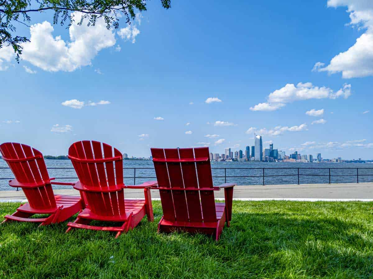 Red wooden deck chairs on a green lawn over looking the New York Skyline.
