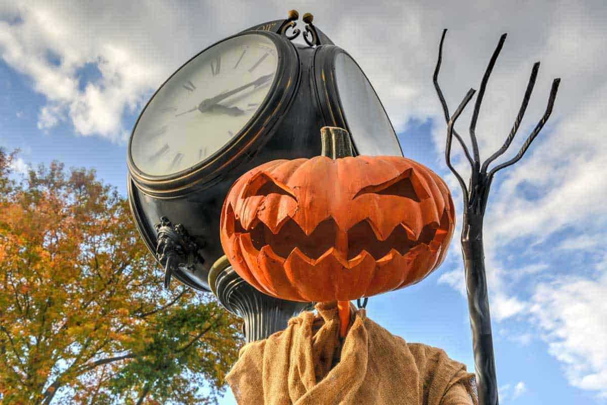 Jackolantern next to an old fashioned street clock.
