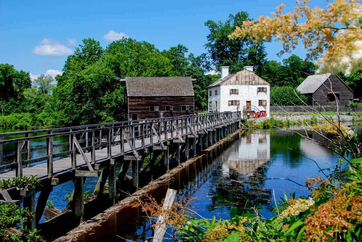 Old White millhouse at the end of a wooden bridge in Sleepy Hollow.