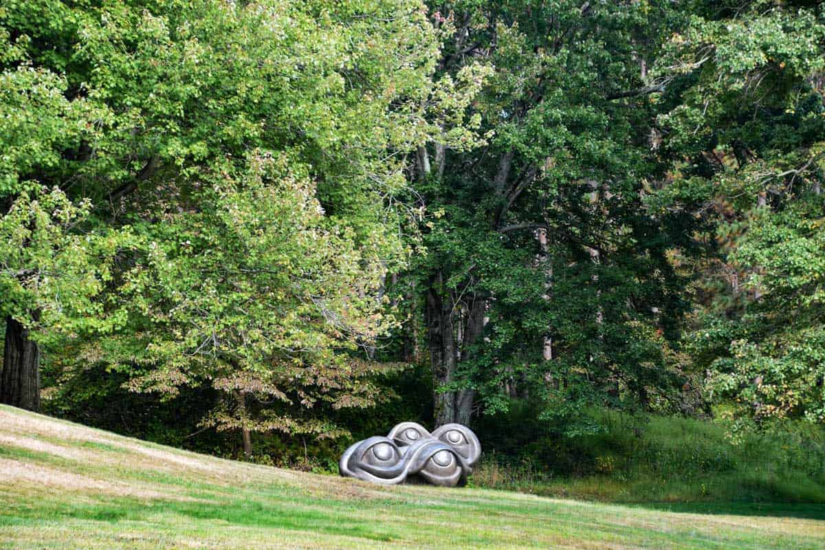 Large abstract sculpture of eyes in a garden setting.