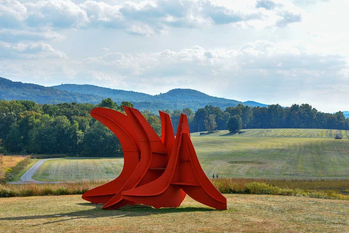 Large red abstract sculpture in a field.