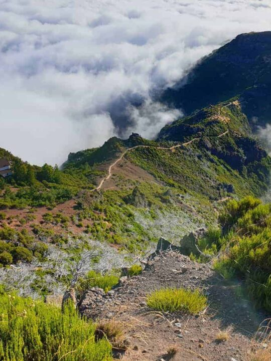 Hiking trail and house on a mountain peak above the clouds on Madeira Island.