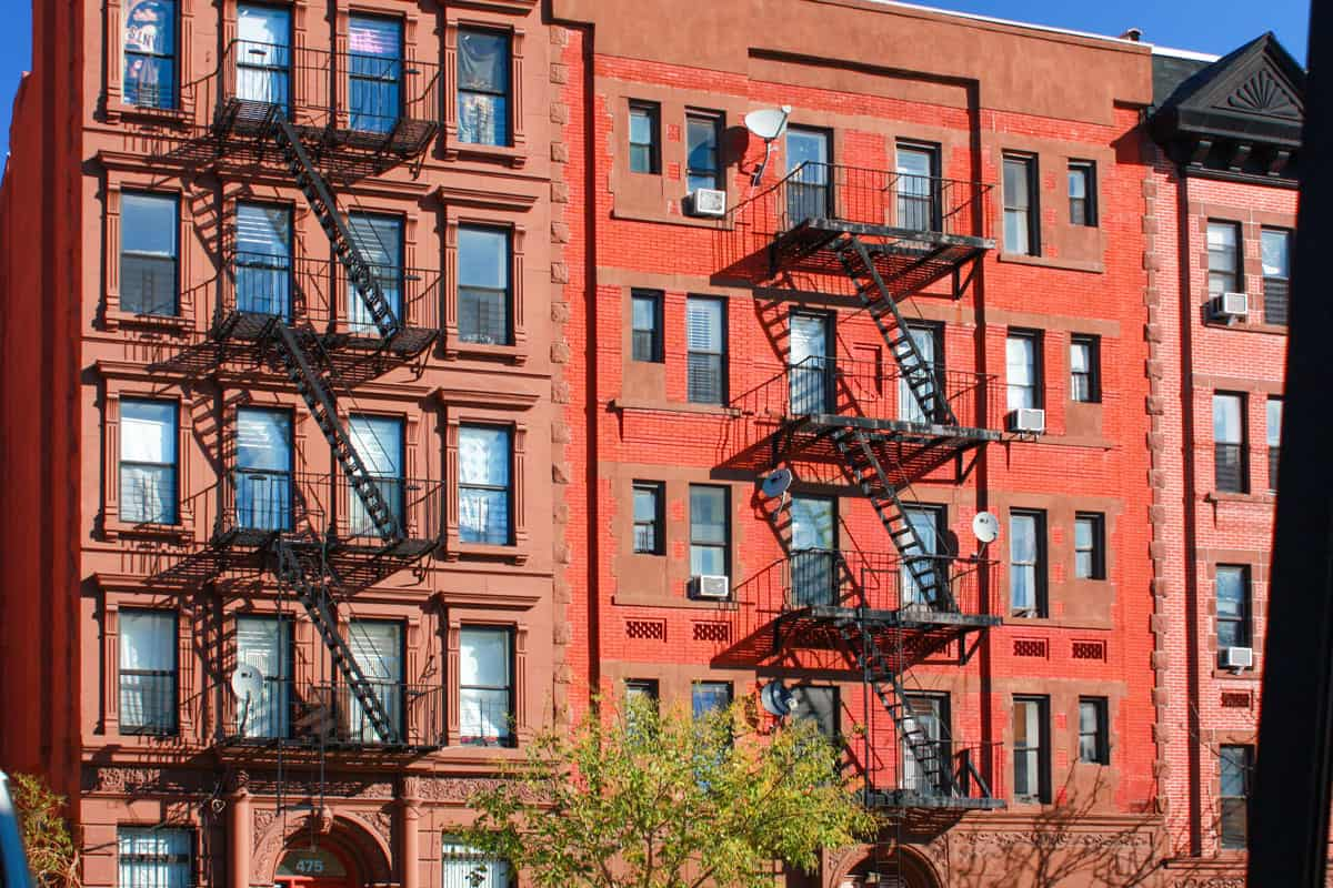 Iconic brick apartment buildings in Harlem with external fire escape stairs.