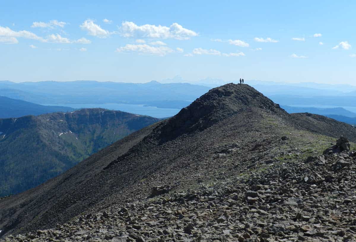 Hikers on a summit peak in the distance on Avalanche hiking trail in Yellowstone NP.