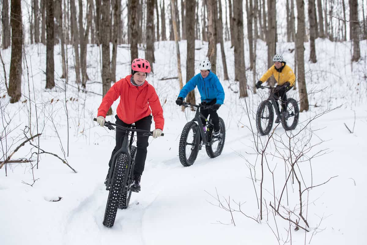 Group of three people fat tire biking in the snow.