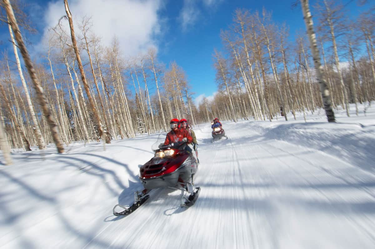 A couple travelling fast on a snowmobile.