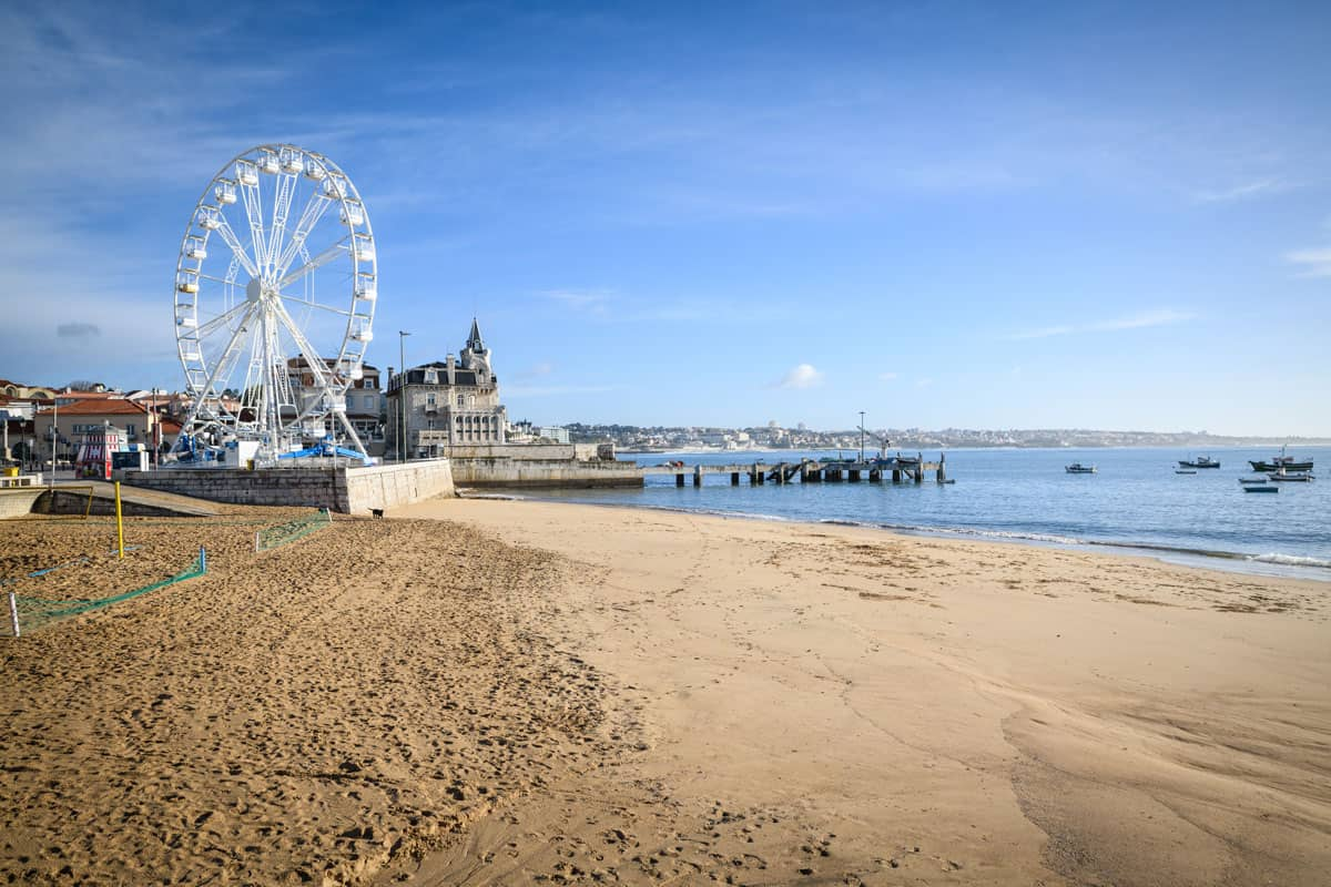 Cascais Beach in Portugal with a ferris wheel on the foreshore.