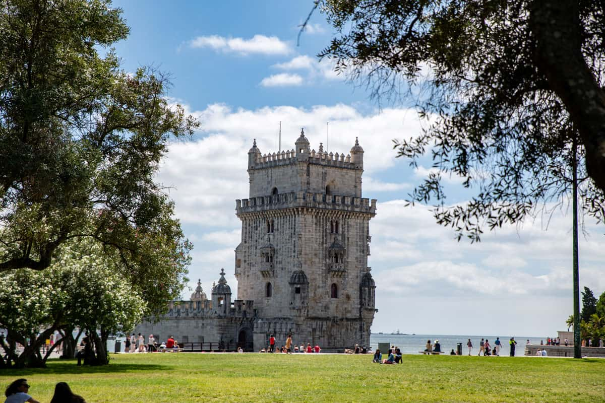 Tower of Belem in Lisbon with people enjoying the surrounding park.
