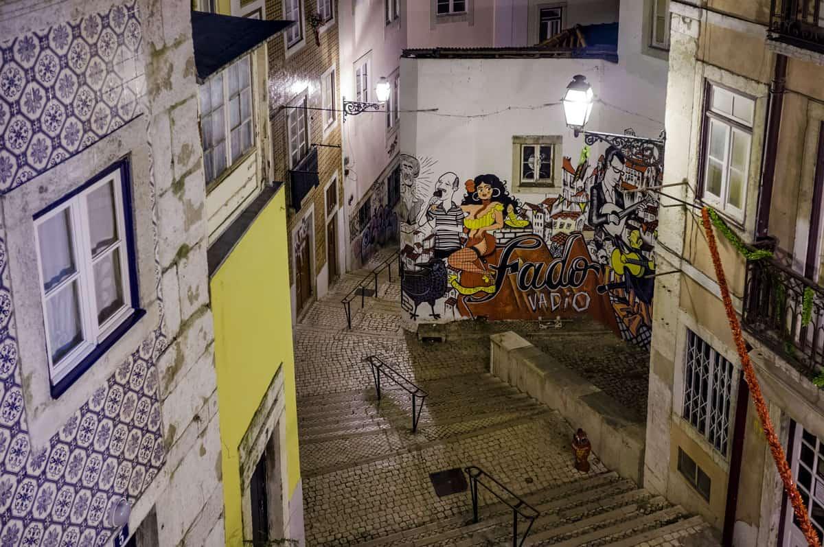 Narrow streets of Alfama with a Fado mural.