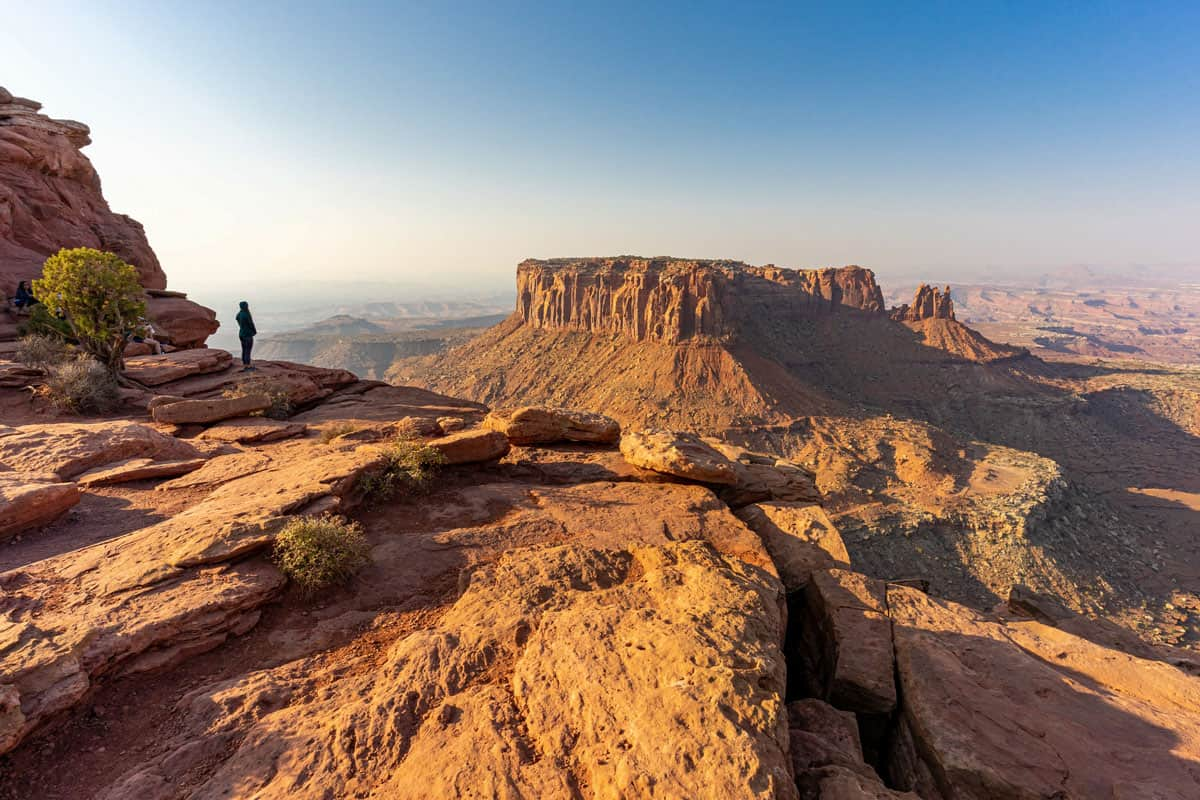 People standing on a cliff edge admiring the view in Moab Utah.