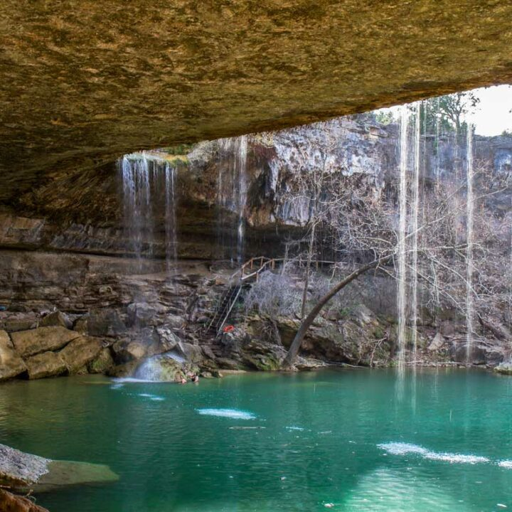 Behind the waterfall at Hamilton Pool Preserve with clear blue swimming hole.
