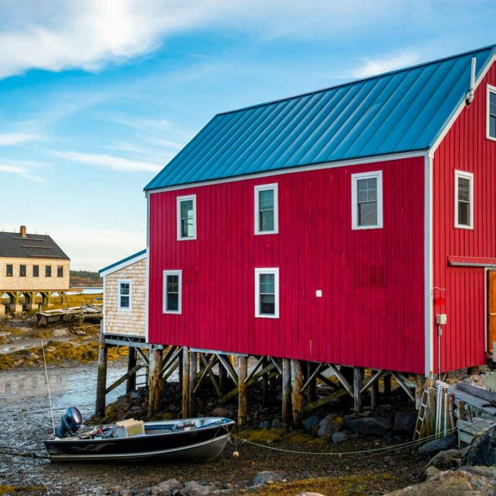 Brigh red fishing shacks over the water in Maine.