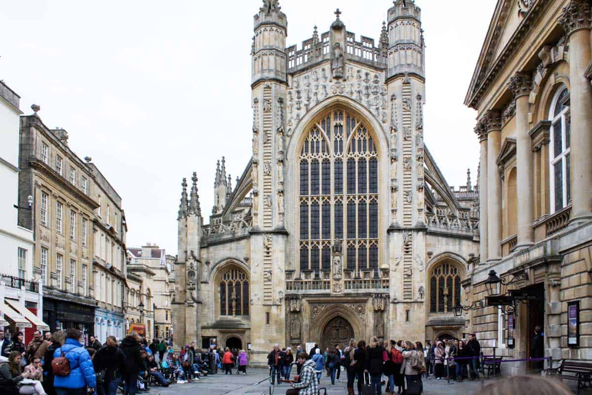 Exterior of Bath Abbey with pedestrians and buskers in front.