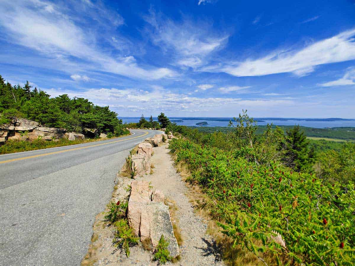 Road with ocean view in the distance on the park Loop Drive in Maine.