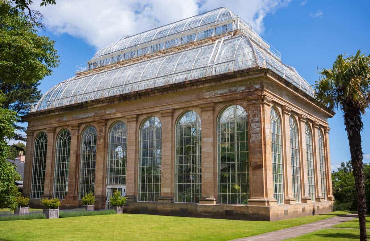 The Palm House on the Edinburgh Royal Botanic Gardens on a sunny day.