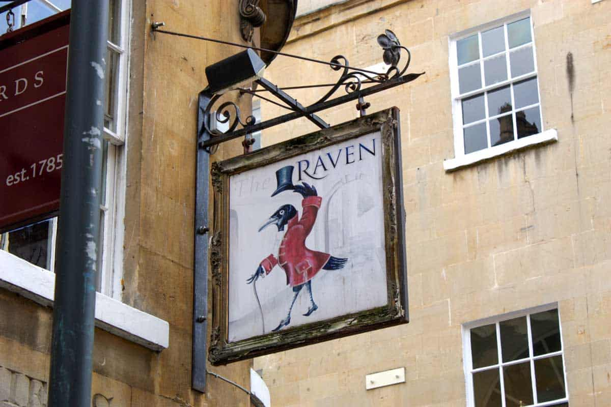 Sign for the Raven Pub with a Raven wearing a top hat.