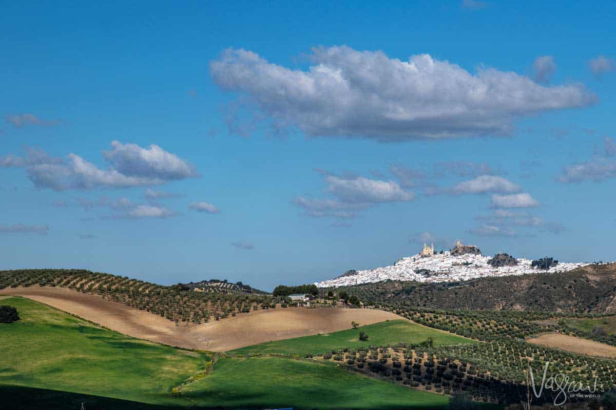 White village in Spain on top of a hill with green meadows in the foreground.