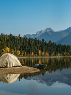 small tent on the banks of a lake reflected in the water.