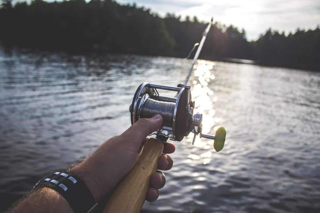 Hand holding a fishing rod over the water at sunset.