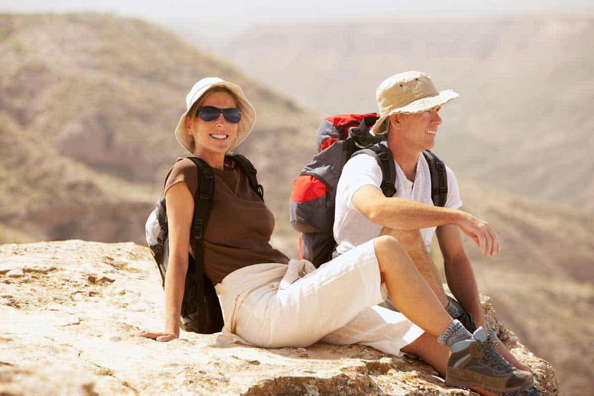 Young hiking couple resting on a rock outcrop in Spain.