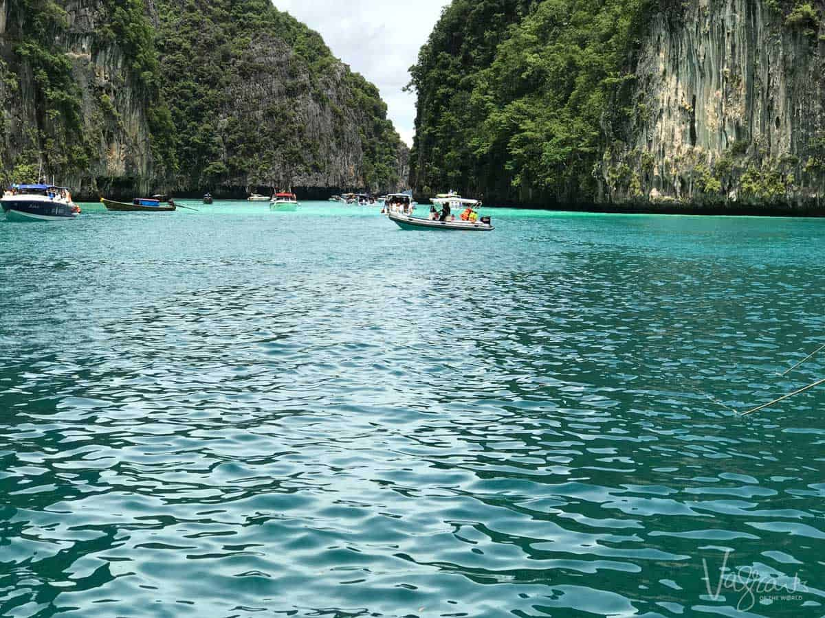 Boats moored in a bay surrounded by cliffs in Thailand.