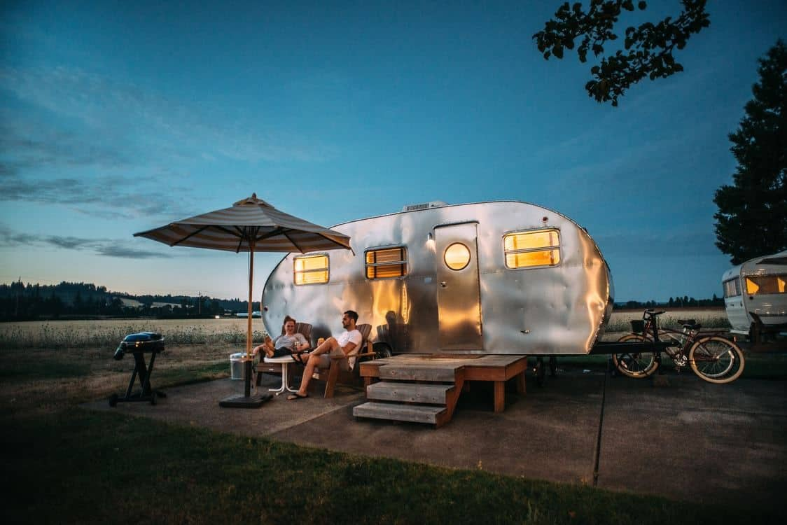 Couple sitting in front of a silver retro caravan at a campsite.