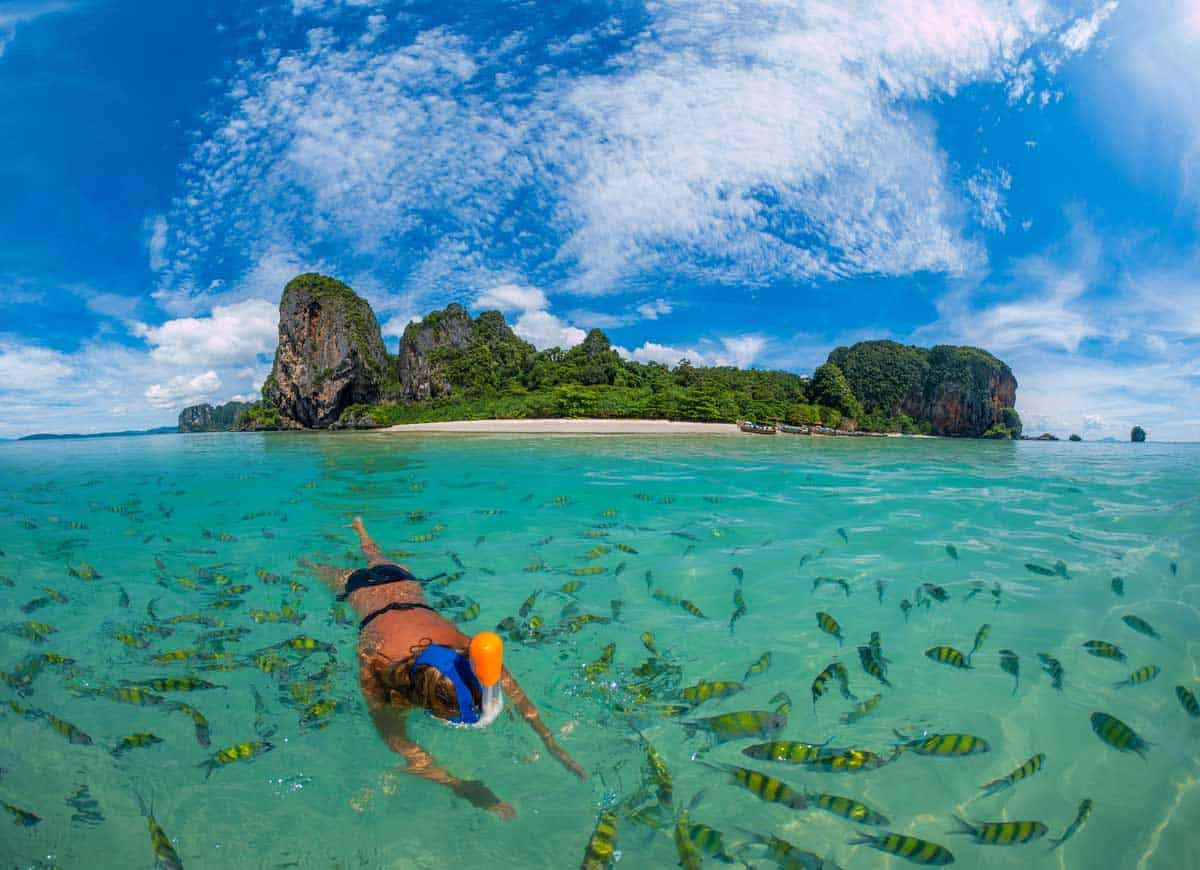 Woman snorkelling in clear water surrounded by fish in Thailand.