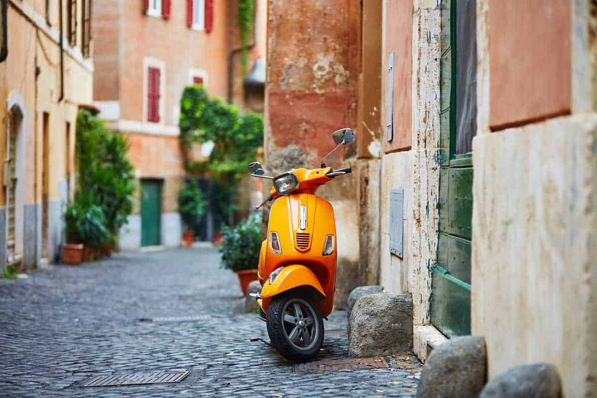 A classic Vespa scooter in the cobble streets of Trastevere in Rome.