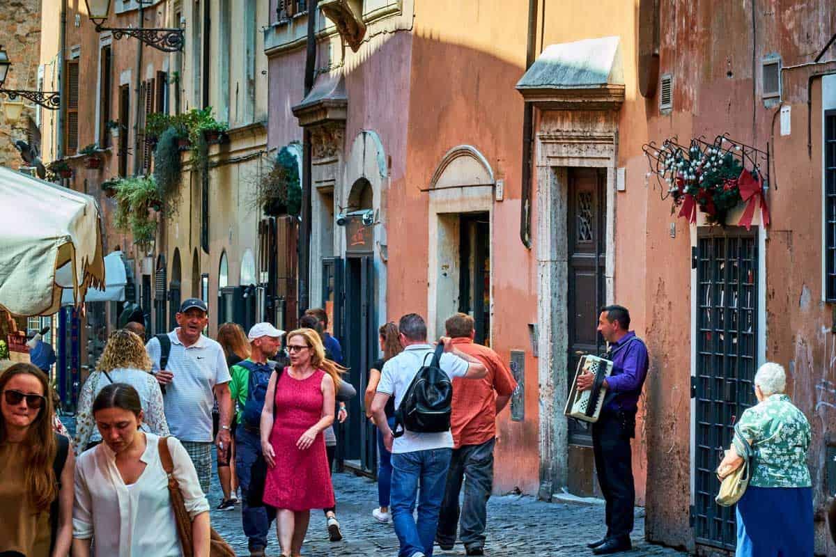 Tourists walking through Trastevere Neighborhood in Rome.