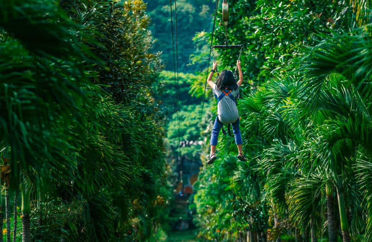 Young girl on a zipline in the Thai forrest.